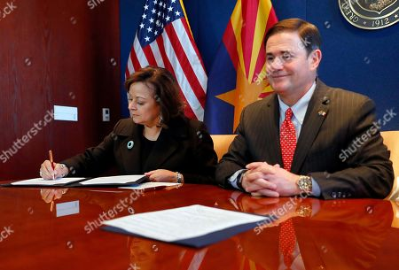 New Mexico Gov. Susana Martinez, left, signs an agreement to a cross-border plan to provide natural gas to Asia as Arizona Gov. Doug Ducey, R, looks, at the Capitol in Phoenix