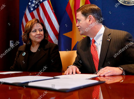 Stock Image of Arizona Gov. Doug Ducey, right, speaks with New Mexico Gov. Susana Martinez, left, prior to signing an agreement to a cross-border plan with Mexico to provide natural gas to Asia., at the Capitol in Phoenix