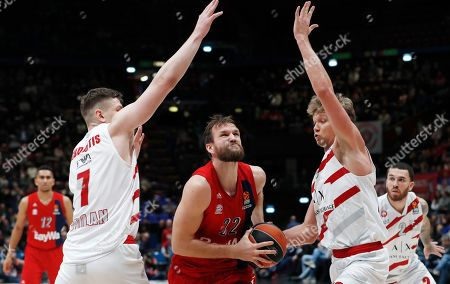 Bayern Munich's Danilo Barthel, center, goes for a basket as Olimpia Milan's Arturas Gudaitis, left, and Mindaugas Kuzminskas trie to stop him during the Euro League basketball match between Olimpia Milan and Bayern Munich, in Milan, Italy