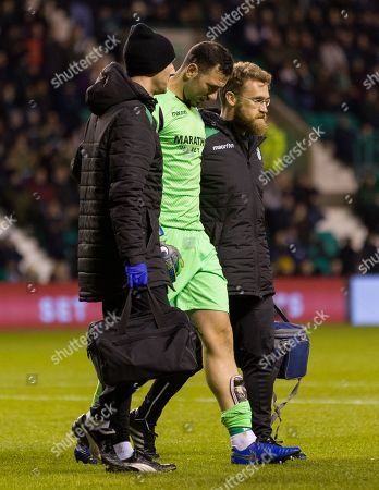 Hibernian goalkeeper Ofir Marciano limps off the pitch injured before being replaced by Adam Bogdan.