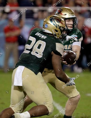 UAB quarterback Tyler Johnston III, right, hands off to running back Spencer Brown (28) during the second half of the Boca Raton Bowl NCAA college football game against Northern Illinois, in Boca Raton, Fla. UAB won 37-13