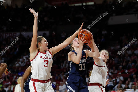 Stock Photo of Connecticut guard/forward Katie Lou Samuelson (33) goes to the basket between Oklahoma forward Mandy Simpson (3) and guard Taylor Robertson (30) during the first half of an NCAA college basketball game in Norman, Okla