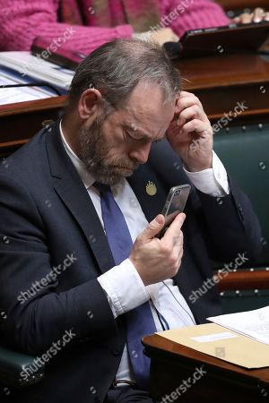 Stock Photo of Leader of Belgium's NVA party, Peter De Roover looks at his phone during a session at Belgian Federal Parliament in Brussels
