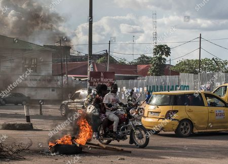 Motorists drive past tires set alight by opposition supporters after the electoral commission announced that the poll will be delayed by one week, in Kinshasa, Democratic Republic of the Congo, 20 December 2018. The head of Congo's electoral commission Corneille Nangaa announced on 20 December that the poll, orignially scheduled for 23 December will be delayed by one week until 30 December, citing the recent fire that destroyed 80 percent of the voting machines. Emmanuel Ramazani Shadary, the ruling party candidate and a loyalist of outgoing president Joseph Kabila, faces challenges posed by Felix Tshisekedi, the leader of the Union for Democracy and Social Progress (UDPS) party, and the joint opposition candidate Martin Fayulu.