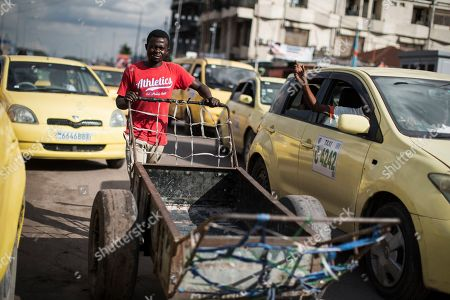 A man pushes through a cart through a busy street in Kinshasa, Democratic Republic of the Congo, 20 December 2018. The head of Congo's electoral commission Corneille Nangaa announced on 20 December that the poll, orignially scheduled for 23 December will be delayed by one week until 30 December, citing the recent fire that destroyed 80 percent of the voting machines. Emmanuel Ramazani Shadary, the ruling party candidate and a loyalist of outgoing president Joseph Kabila, faces challenges posed by Felix Tshisekedi, the leader of the Union for Democracy and Social Progress (UDPS) party, and the joint opposition candidate Martin Fayulu.