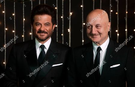 Bollywood actors Anil Kapoor, left and Anupam Kher pose for photographs at Priyanka Chopra and musician Nick Jonas wedding reception in Mumbai, India