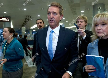 Sen. Jeff Flake, R-Ariz., a member of the Senate Foreign Relations Committee, speaks with reporters on his way to the senate chamber, as the Senate takes up a House-passed bill that would pay for President Donald Trump's border wall and avert a partial government shutdown, at the Capitol in Washington