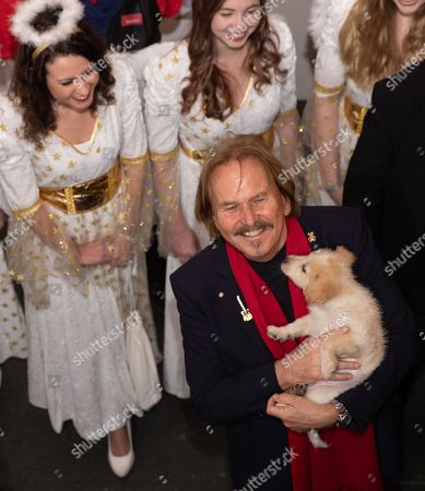 German singer and actor Frank Zander (C) holds a puppy of a homeless woman (unseen) as he receives homeless people for his 24th Christmas party for the homeless in Berlin, Germany, 21 December 2018. Zander and around 200 helpers held a Christmas party for about 3,000 homeless people.