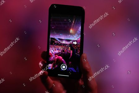Darts fan takes a photo on his mobile phone during the World Darts Championships 2018 at Alexandra Palace, London