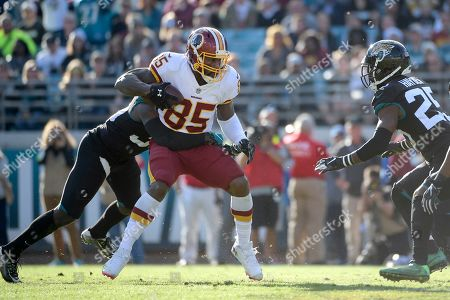 Washington Redskins tight end Vernon Davis (85) catches a pass between Jacksonville Jaguars free safety Tashaun Gipson, left, and defensive back D.J. Hayden (25) during the second half of an NFL football game, in Jacksonville, Fla