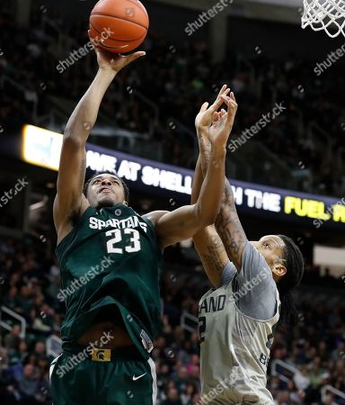 Xavier Tillman, James Beck. Michigan State forward Xavier Tillman (23) shoots as Oakland forward James Beck (22) defends during the second half of an NCAA college basketball game, in East Lansing, Mich