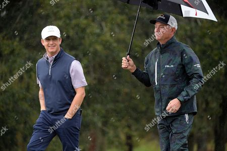David Toms, left, and Davis Love III walk on the second fairway after hitting their tee shots during the first round of the Father Son Challenge golf tournament, in Orlando, Fla