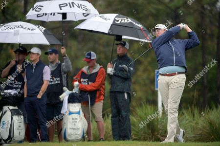 David Toms, second from left, and Davis Love III, second from right, watch the flight of the ball after Dru Love, right, hits his tee shot on the second hole during the first round of the Father Son Challenge golf tournament, in Orlando, Fla