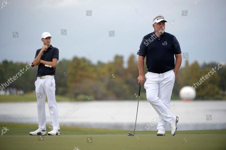 Darren Clarke, right, and his son, Tyrone Clarke, wait to putt on the 18th green during the first round of the Father Son Challenge golf tournament, in Orlando, Fla