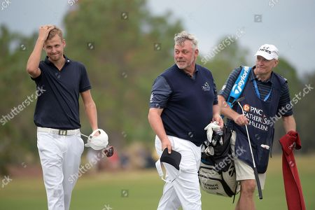 Darren Clarke, center, and his son, Tyrone Clarke, left, acknowledge the crowd after putting on the 18th green during the first round of the Father Son Challenge golf tournament, in Orlando, Fla