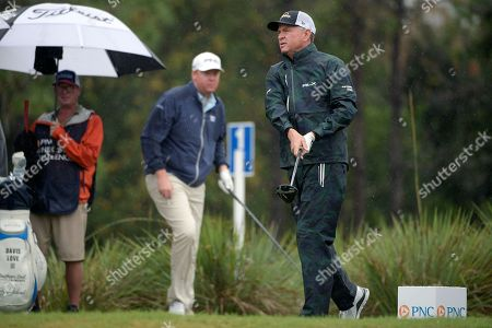 Dru Love, center, watches as his father, Davis Love III, right, tees off on the second hole during the first round of the Father Son Challenge golf tournament, in Orlando, Fla