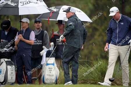 David Toms, second from left, and Davis Love III, second from right, watch the flight of the ball after Love hit his tee shot on the second hole, as Dru Love, right, sets up to tee off during the first round of the Father Son Challenge golf tournament, in Orlando, Fla