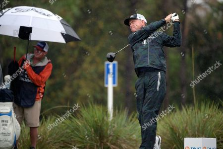 Davis Love III, right, watches his tee shot on the second hole during the first round of the Father Son Challenge golf tournament, in Orlando, Fla