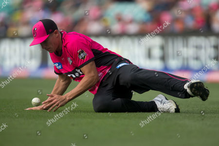 Sydney Sixers player Sean Abbott slides to stop the ball at the Big Bash League cricket match between Sydney Sixers and Perth Scorchers at The Sydney Cricket Ground in Sydney, Australia