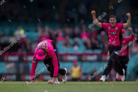 Sydney Sixers player Daniel Hughes takes a catch as Sydney Sixers player Sean Abbott celebrates at the Big Bash League cricket match between Sydney Sixers and Perth Scorchers at The Sydney Cricket Ground in Sydney, Australia