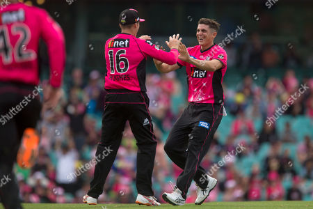 Sydney Sixers player Daniel Hughes and Sydney Sixers player Sean Abbott celebrate a wicket at the Big Bash League cricket match between Sydney Sixers and Perth Scorchers at The Sydney Cricket Ground in Sydney, Australia