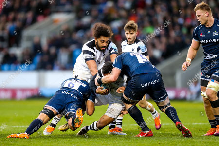 Siale Piutau (co-capt) of Bristol Bears is tackled by Jono Ross (capt) and James Phillips of Sale Sharks
