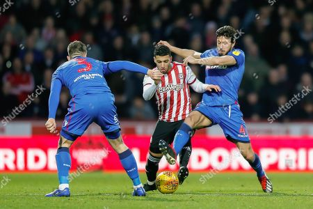 Brentford attacker Saïd Benrahma (21) battles with Bolton Wanderers defender Andrew Taylor (3) and Bolton Wanderers midfielder Jason Lowe (4) during the EFL Sky Bet Championship match between Brentford and Bolton Wanderers at Griffin Park, London