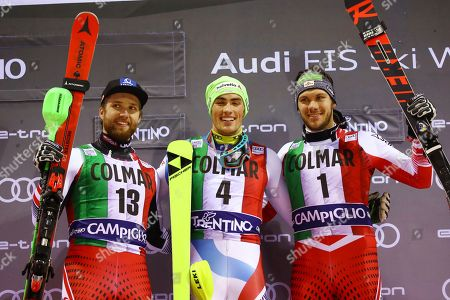 Stock Image of From left, second placed Austria's Marco Schwarz, first placed Switzerland's Daniel Yule and third placed Austria's Michael Matt celebrate on the podium at the end of a ski World Cup Men's Slalom, in Madonna Di Campiglio, Italy
