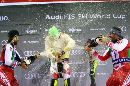 From left, second placed Austria's Marco Schwarz, first placed Switzerland's Daniel Yule and third placed Austria's Michael Matt celebrate on the podium with sparkling wine at the end of a ski World Cup Men's Slalom, in Madonna Di Campiglio, Italy