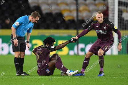Wilfried Bony of Swansea City is helped up by team-mate Mike van der Hoorn