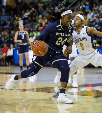 Notre Dame's Arike Ogunbowale, left, drives to the basket against Marquette's Danielle King, right, during the first half of an NCAA women's college basketball game, in Milwaukee