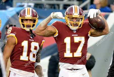 Washington Redskins wide receiver Michael Floyd (17) celebrates after scoring a touchdown against the Tennessee Titans in the first half of an NFL football game, in Nashville, Tenn. At left is wide receiver Josh Doctson (18