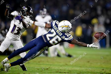 Los Angeles Chargers cornerback Casey Hayward tries to intercept a pass intended for Baltimore Ravens wide receiver John Brown during the second half in an NFL football game, in Carson, Calif
