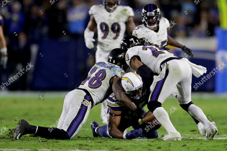 Baltimore Ravens inside linebacker Patrick Onwuasor, left, and cornerback Brandon Carr force a fumble by Los Angeles Chargers tight end Antonio Gates during the second half in an NFL football game, in Carson, Calif