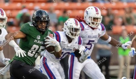 Stock Image of Hawaii wide receiver Marcus Armstrong-Brown (85) runs with the football while being pursued by Louisiana Tech safety James Jackson (10) and cornerback Michael Sam (5) in the first half of the Hawaii Bowl NCAA college football game, in Honolulu