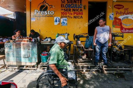 In this Dec. 21. 2018 photo, a man stands outside a tailor shop displaying photos of President Daniel Ortega and his wife and Vice President Rosario Murillo, in Managua, Nicaragua. . In the streets of Managua, outward appearances suggest some degree of normality. But vendors say business has been running 25 to 30 percent below what it was last year, even in the run-up to Christmas