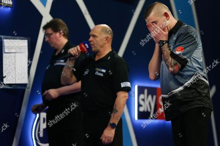 WINNER Nathan Aspinall holds his face after winning his Third Round match against Kyle Anderson during the World Darts Championships 2018 at Alexandra Palace, London