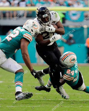 Raekwon McMillan, Torry McTyer, Leonard Fournette. Miami Dolphins middle linebacker Raekwon McMillan (52) and cornerback Torry McTyer (24) tackle Jacksonville Jaguars running back Leonard Fournette (27), during the second half at an NFL football game, in Miami Gardens, Fla