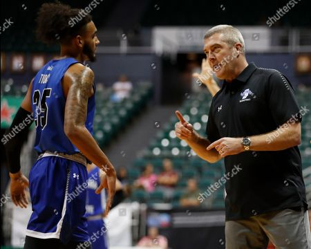 Stock Photo of Indiana State head coach Greg Lansing speaks to Indiana State forward Devin Thomas (35) during the first half of an NCAA college basketball game at the Diamond Head Classic, in Honolulu