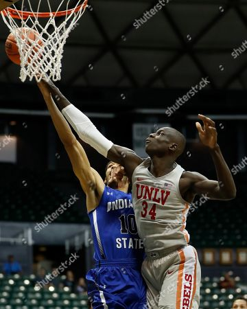 UNLV forward Cheikh Mbacke Diong (34) fouls Indiana State guard Christian Williams (10) during the first half of an NCAA college basketball game at the Diamond Head Classic, in Honolulu