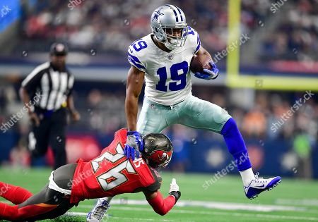 Dallas Cowboys wide receiver Amari Cooper #19 catches a pass as he tries to elude Tampa Bay Buccaneers safety Andrew Adams #26 during an NFL football game between the Tampa Bay Buccaneers and Dallas Cowboys at AT&T Stadium in Arlington, Texas
