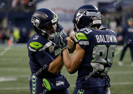 Seattle Seahawks quarterback Russell Wilson, left, greets wide receiver Doug Baldwin, right, during warmups before an NFL football game against the Kansas City Chiefs, in Seattle