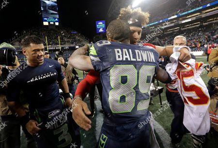 Seattle Seahawks wide receiver Doug Baldwin (89) hugs Kansas City Chiefs quarterback Patrick Mahomes as Seahawks quarterback Russell Wilson looks on at left after an NFL football game, in Seattle. The Seahawks won 38-31