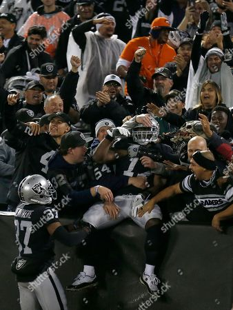 Oakland Raiders' Dwayne Harris, center, celebrates with fans after returning a punt for a touchdown against the Denver Broncos during the first half of an NFL football game in Oakland, Calif