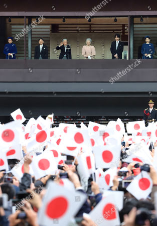 Wellwishers wave Japanese national flags as Japanese Emperor Akihito (3rd L), Empress Michiko (3rd R), Crown Prince Naruhito (2nd L), Crown Princess Masako (L), Prince Akishino (2nd R) and Princess Akishino (R) appear on the balcony of the Imperial Palace in Tokyo on Sunday, December 23, 2018. Emperor Akihito celebrated his 85th birthday and he has plan to adbicate on April 30 next year.