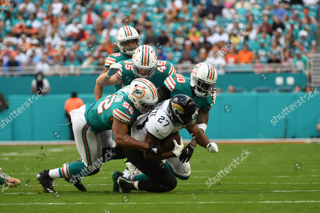 Reshad Jones #20, Mike Hull #45, and Raekwon McMillan #52 of Miami tackle Leonard Fournette #27 of Jacksonville during the NFL football game between the Miami Dolphins and Jacksonville Jaguars at Hard Rock Stadium in Miami Gardens FL. The Jaguars defeated the Dolphins 17-7