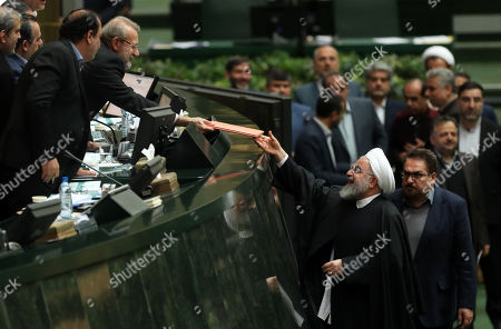 Iranian President Hassan Rouhani (R) delivers budget papers to Parliament Speaker Ali Larijani (L) during the parliament session in Tehran, Iran, 25 December 2018. According to reports, Rouhani said in his speech that US, by forcing sanctions against the country, hits the lives, development and economic growth. Rouhani presented the budget draft at about 4,700 trillion Iranian Rials for the next Iranian year which starts on 21 March 2019.