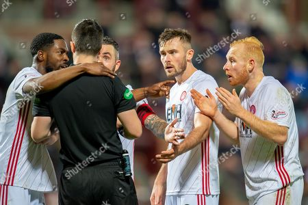 Ziggy Gordon (#4) and Aaron McGowan (#2) of Hamilton Academical FC argue with referee Nick Walsh after he gives a penalty against Hamilton during the Ladbrokes Scottish Premiership match between Heart of Midlothian FC and Hamilton Academical FC at Tynecastle Stadium