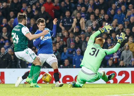 Stock Image of Darren McGregor of Hibernian touches the ball away from Glenn Middleton of Rangers just before he shoots at goal, with Hibernian goalkeeper Adam Bogdan, right.