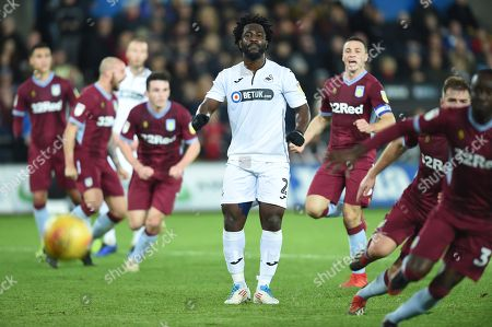 Wilfried Bony of Swansea City looks dejected as he misses a shot from the penalty spot as James Chester of Aston Villa celebrates in the background.